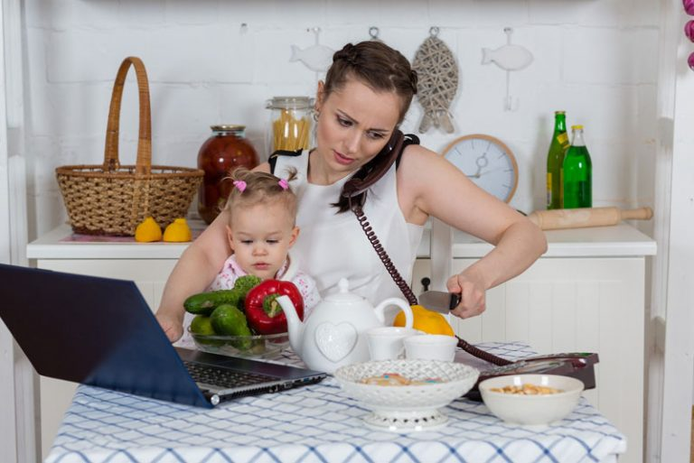 Working Mother With Baby In Kitchen
